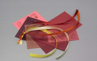Image of Red, Yellow, and Orange Satin Ribbon on Red Cardstock