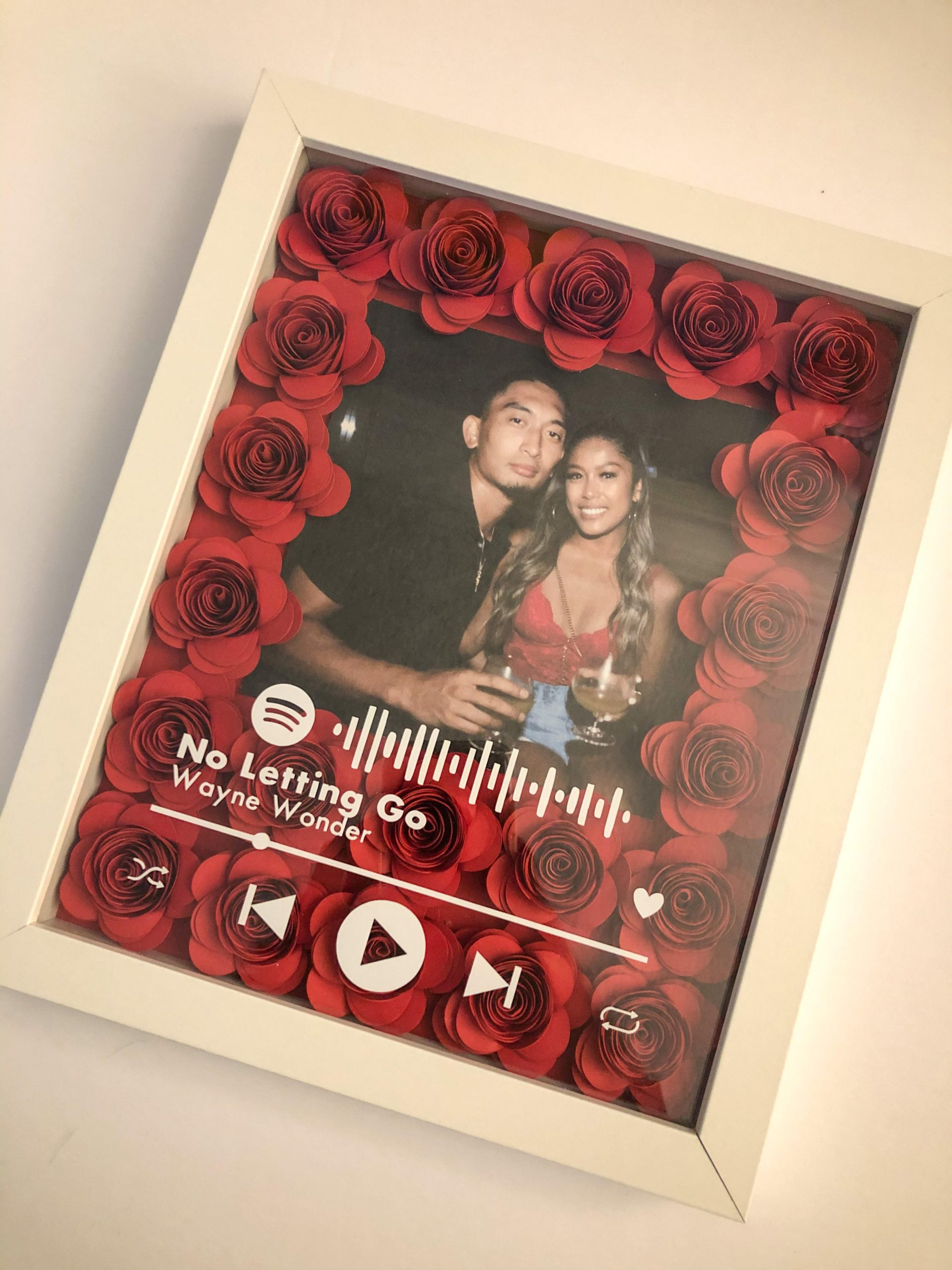 Image of a flower box with a customer's couples photo inside made to look like a Spotify window playing a love song