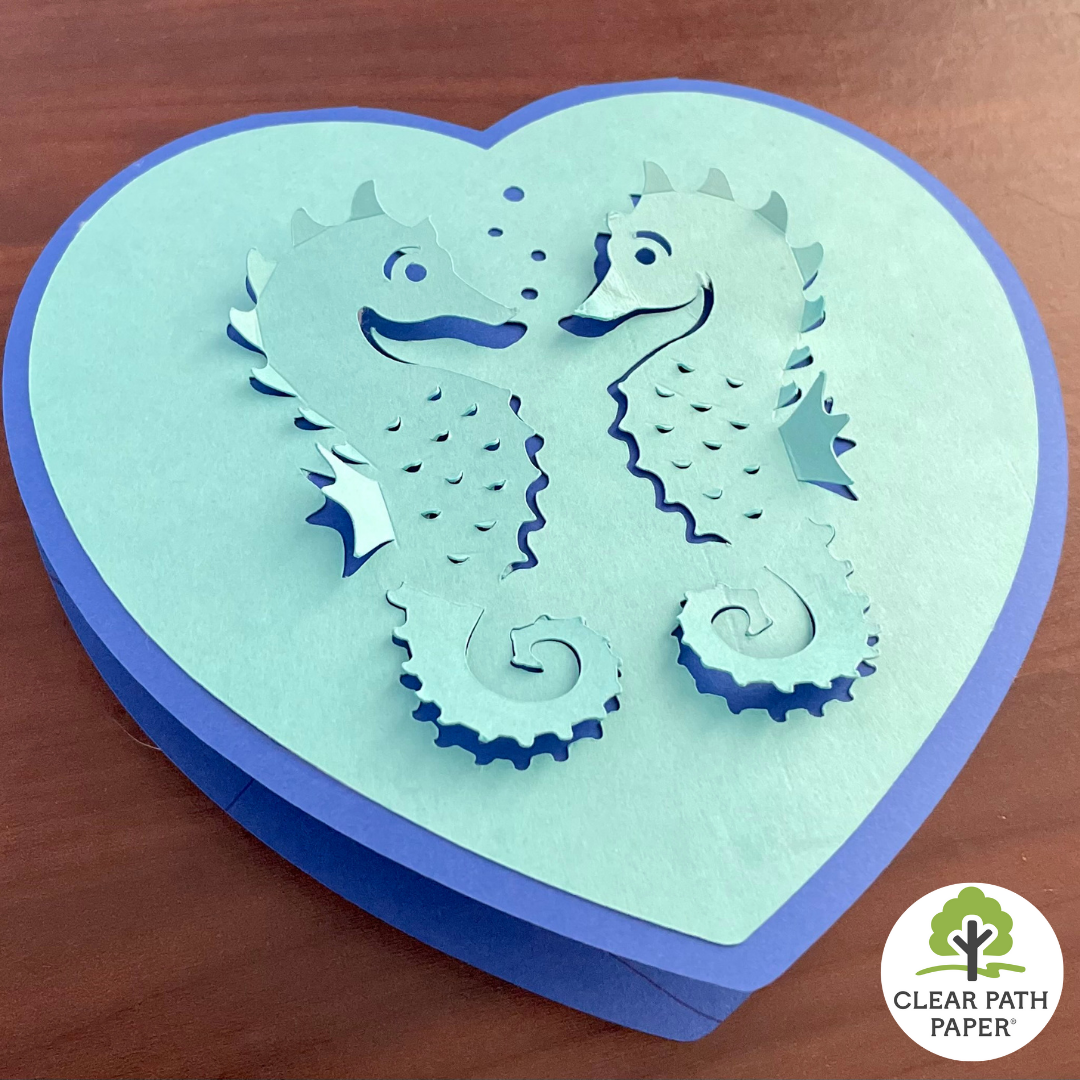 Image of a heart-shaped diecut greeting card with 3D seahorses on it made from Clear Path Paper cardstock